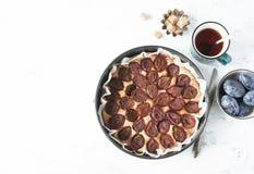 Whole plum cake with tea mug, fresh plums and brown sugar. Top v Stock Image