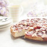 Whole plum cake with tea mug, plates and flowers on background. Royalty Free Stock Photography
