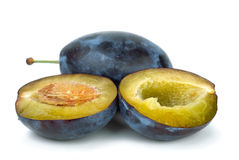 Whole plum and halves. Isolated on the white background Royalty Free Stock Photo