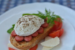 Whole poached egg on sandwich, decorated with tomato, cheese, herb on white plate. Whole, spiced poached egg on sausage, bread, cheese, tomato on plate Royalty Free Stock Photos