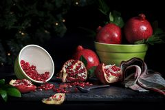 Whole Pomegranates and Seeds in Bowl. Several whole pomegranates as well as open with seeds exposed, a small bowl of seeds spilled over with seeds pouring onto Royalty Free Stock Images