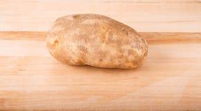 Whole Potato on Wood Cutting Board Stock Photos