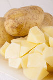 Whole Potatoes and Chopped Pieces on Cutting Board Royalty Free Stock Image