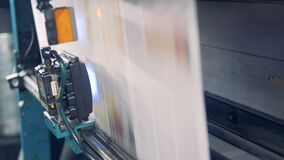 Whole printed web of paper is moving down the industrial machine stock video