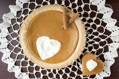 Whole pumpkin pie with a heart shape cut out with piece lying beside the pie with whipped cream. Royalty Free Stock Image