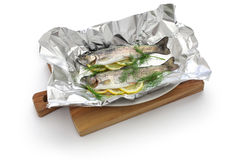 Whole rainbow trout baked in foil (before oven baking). On white background stock photos