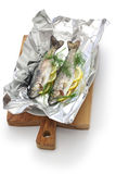 Whole rainbow trout baked in foil (before oven baking). On white background stock image