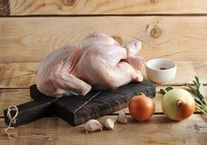 Whole raw chicken carcass on the Board and spices. On wooden rustic background Royalty Free Stock Image