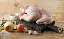 Whole raw chicken carcass on the Board and spices. On wooden rustic background Stock Photography