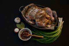 Whole raw chicken. Closeup of whole raw chicken on a frying pan, garlic, green onion, color pepper, bay leaves and other spices  on dark background Royalty Free Stock Photos