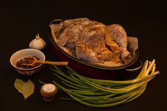 Whole raw chicken. Closeup of whole raw chicken on a frying pan, garlic, green onion, color pepper, bay leaves and other spices  on dark background Stock Photos
