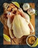 Whole Raw Chicken with ingredients for cooking. on stone background Stock Photography