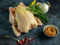 Whole Raw Chicken with ingredients for cooking. on stone background.  Royalty Free Stock Photos