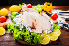 Whole Raw Chicken with ingredients for cooking. on wooden backgr Royalty Free Stock Images