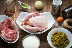 Whole raw chicken with ingredients on wooden background royalty free stock image