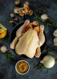 Whole Raw Chicken in iron pan, with ingredients for cooking. on stone background.  Stock Photography