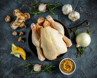 Whole Raw Chicken in iron pan, with ingredients for cooking. on stone background.  Stock Photo