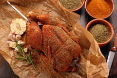 Whole raw chicken with spices ready for roasting on a spit Stock Photo