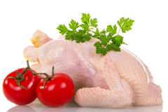 Whole raw chicken, tomatoes and parsley isolated on white. Royalty Free Stock Images