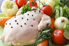 Whole raw chicken with vegetables. And pepper royalty free stock image