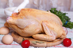 Whole raw chicken. On a wooden board Stock Image