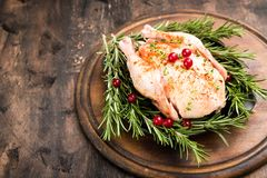 Whole raw chicken on wooden cutting board. raw chicken carcass. With spices Stock Photography