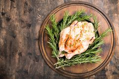 Whole raw chicken on wooden cutting board. raw chicken carcass. With spices Stock Photo
