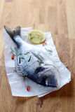 Whole raw fish on crumpled paper. Lying on a wooden kitchen table waiting to be filleted to cook as an enjoyable seafood dinner Royalty Free Stock Images