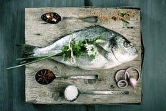 Whole Raw Fish on Cutting Board with Seasonings Stock Image
