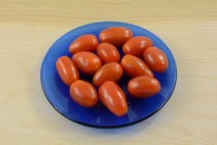 Whole raw grape tomatoes. In small blue plate on wooden table Royalty Free Stock Photo