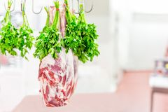 Whole raw lamb leg hanged on hook with bunch of parsley at market or shop. Meat prepared for cook.  royalty free stock photography