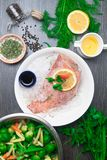 Whole raw organic fish sea perch on ice cubes in white plate on a dark table background with black pepper, olive oil, dill, cilant. Ro, hyssop spices, parsley stock images