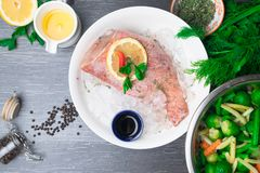 Whole raw organic fish sea perch on ice cubes in white plate on a dark table background with black pepper, olive oil, dill, cilant. Ro, hyssop spices, parsley royalty free stock photos