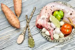 Raw rabbit on a wooden background. A whole, raw rabbit with vegetables and spices on a wooden background close-up Royalty Free Stock Photo