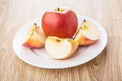 Whole red apple and pieces in white plate on table Stock Photos