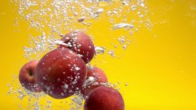 Whole red apples falling under water stock video footage