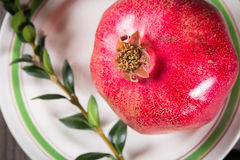 Whole red pomegranate on rustic wooden unpainted table Stock Image