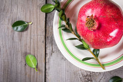 Whole red pomegranate on rustic wooden unpainted table Stock Photo