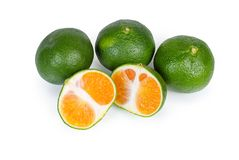 Whole ripe green tangerines and one tangerine cut in half. Several whole ripe green tangerines and one tangerine cut in half on a white background royalty free stock images