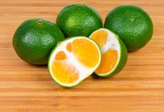 Whole ripe green tangerines and one tangerine cut in half. On a wooden bamboo cutting board royalty free stock photo