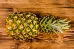 Whole ripe pineapple on a wooden table. Top view royalty free stock photo