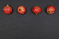 Whole ripe pomegranates in a row on dark grey background stock photography
