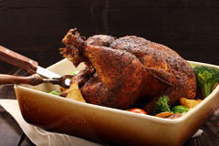 Whole roast chicken with vegetables in bowl on wooden background Royalty Free Stock Images