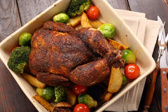 Whole roast chicken with vegetables in bowl Stock Image