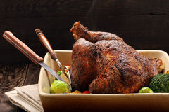 Whole roast chicken with vegetables in bowl on wooden background Stock Photo