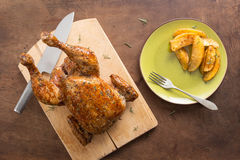 Whole roast chicken on wooden table Royalty Free Stock Photos