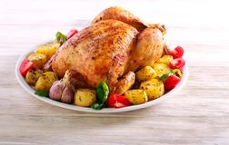 Whole roast spicy chicken with potatoes. On plate over wooden background royalty free stock photos