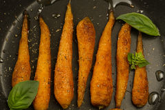 Whole roasted carrots with spices in a skillet. Stock Photo