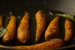 Whole roasted carrots with spices in a skillet. Royalty Free Stock Photo