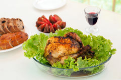 Whole roasted chicken with green salad on table Royalty Free Stock Images
